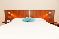 Hotel Bedroom. Modern hotel bedroom with white bed, wooden furniture, two blue cushions, telephone and two lamps. Horizontal view royalty free stock photo