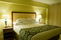 Hotel bedroom. A view of a comfortable, well-furnished hotel bedroom with nightstands and lamps at night Stock Photos