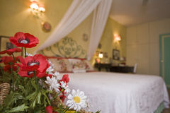 Hotel bedroom. Flowers in a bedroom with double bed and lamp in the background Stock Photo