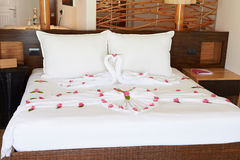 Hotel Bedroom With Flowers Arranged On Sheets Stock Photo