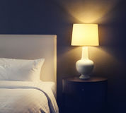 Hotel bedroom with lamp and hotel bed with space for text Royalty Free Stock Images
