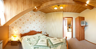 Hotel bedroom panorama. Panorama of an elegant hotel bedroom with wooden ceiling, double bed and TV set Stock Photography