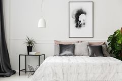 Hotel bedroom with plants. Bright hotel bedroom interior with fresh potted plants, books on metal table and poster on the wall royalty free stock photo