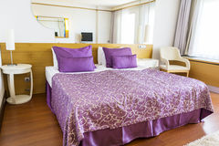 Hotel bedroom in purple with classic bed Royalty Free Stock Images