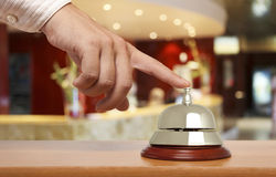 Hotel bell. Hand of a man using a hotel bell Royalty Free Stock Photos