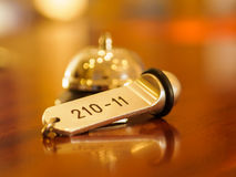Hotel bell and key lying on the desk Royalty Free Stock Photography