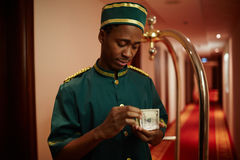 Hotel Bellboy Counting Cash Royalty Free Stock Images