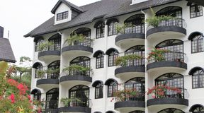 Hotel. Black and white trimmed balconies overlooking garden with red flowers Stock Photo