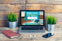Hotel booking in the office. Hotel booking website template in a laptop screen. Computer with other accessories in a wooden desk royalty free stock photos