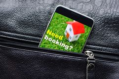 Hotel booking and reservation concept. Smart phone with a toy house on a display looks out from the unzipped pocket stock photography
