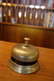 Hotel brass bell. Vintage brass bell on hotel front desk with blurred key rack in the background. Very shallow depth of field with focus on the button Royalty Free Stock Image