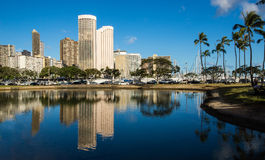 Hotel buildings in Waikiki, Hawaii. Reflected in a blue lagoon Royalty Free Stock Image