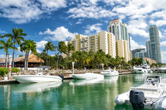 Hotel buildings with yachts and palm trees Stock Images