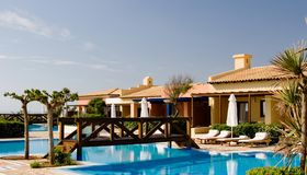 Hotel bungalow and pool. Hotel bungalow and blue swimming pool stock image