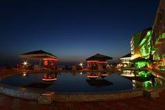 Hotel, café y piscina en noche Imagen de archivo libre de regalías