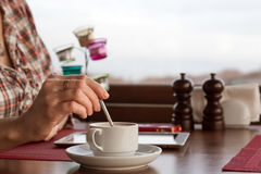 Hotel Cafe Table and human Hand mixing Coffee stock photo