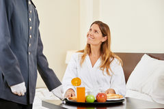 Hotel clerk bringing breakfast as room service. For women in hotel room Stock Image