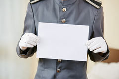 Hotel clerk holding empty white paper Royalty Free Stock Image