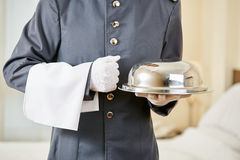 Hotel clerk serving food with cloche. In a hotel room Stock Images