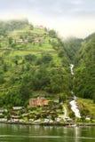 Hotel and coastal village under mountain. Hotel and coastal village under green mountain with waterfall Stock Image