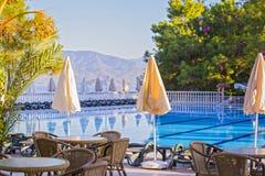 Hotel comodo di palazzo multipiano Hotel vuoto, piscina, mare, palme, ombrelli, tavole, letti del sole, montagne nei precedenti Fotografie Stock Libere da Diritti
