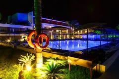 Hotel con la piscina e palma al conservatore di vita di notte in priorità alta Immagini Stock Libere da Diritti