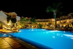 Hotel con la piscina en la noche Foto de archivo libre de regalías