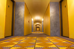 Hotel corridor. Empty hotel corridor illuminated with yellowish light Royalty Free Stock Photo