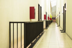 Hotel Corridor. Perspective view of hotel room corridor with stretch of fire extinguisher box and iron railing Stock Image
