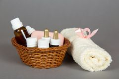Hotel cosmetics kit and terry towel in basket. On a grey background Royalty Free Stock Photos