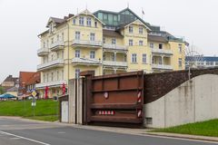 Hotel Cuxhaven with steel door in dike for water protection. CUXHAVEN, GERMANY - MAY 19, 2017: Hotel `Haus Continental` in Cuxhaven with steel door in dike for Stock Photos