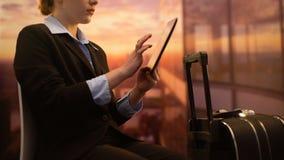 Hotel de la reservación de la mujer en la tableta mientras que espera el vuelo en el aeropuerto, viaje de negocios metrajes