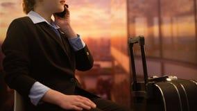 Hotel de reservación de la señora por el teléfono mientras que espera el vuelo en el aeropuerto, viaje de negocios almacen de video