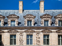 Hotel de Sully Paris France. Detail of the facade of Hotel de Sully historical building with its adornments, grey roof, chimneys and bas reliefs, Paris, France Royalty Free Stock Photos