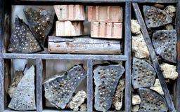 Hotel del insecto con los registros de los ladrillos, del grupo de la arcilla y maderas Fotos de archivo libres de regalías