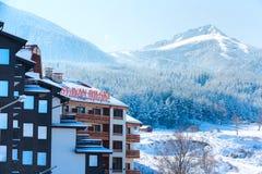 Hotel del St Ivan Rilski y panorama de las montañas de la nieve en la estación de esquí búlgara Bansko Foto de archivo