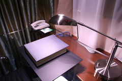 Hotel desk and reading lamp. Dictionary on the desk with reading lamp turning on Royalty Free Stock Photos