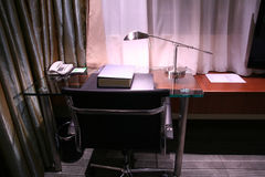 Hotel desk and reading lamp. Dictionary on the desk with reading lamp turning on Royalty Free Stock Image