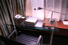 Hotel desk and reading lamp. Dictionary on the desk with reading lamp turning on Royalty Free Stock Photography