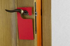 Red Door Hanger. Hotel door handle with blank paper hanger Royalty Free Stock Photo
