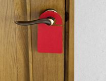 Red Door Hanger. Hotel door handle with blank paper hanger Royalty Free Stock Image