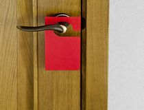 Red Door Hanger. Hotel door handle with blank paper hanger Stock Photo