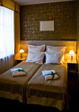 Hotel double bed. Interior of an elegant hotel room, double bed with bedside lamps Stock Images