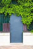 Hotel entrance door with sign in a fence with green foliage Royalty Free Stock Photo