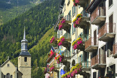 Hotel facade and the church behind in city Chamonix. Stock Images