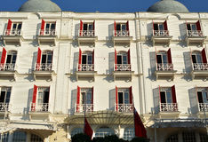 Hotel facade. Historical white hotel facade with red shutters and balconies royalty free stock image