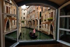 Hotel-Fenster-Ansicht von Venedig-Kanälen, -gebäuden und -gondolieren Stockfotos