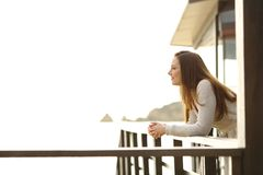Hotel guest contemplating from a balcony on the beach. Side view portrait of a pensive hotel guest contemplating ocean from a balcony on the beach royalty free stock photography
