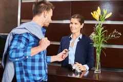 Hotel guest paying with credit card at reception Stock Photos