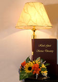 Hotel Guest Service Directory and Lamp. Guest service directory in a dimly lit hotel atmosphere with tropical flowers Royalty Free Stock Images